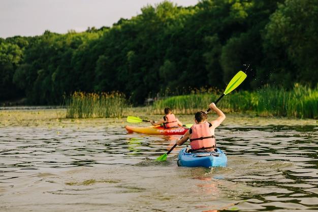 Vista traseira, de, dois, homem, kayaking, ligado, lago