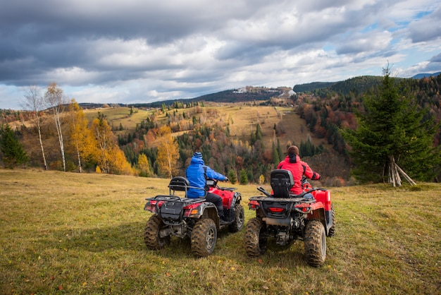 Vista traseira, de, dois homens, sentando, ligado, quad, bicicletas, desfrutando, bonito, paisagem, de, montanhas