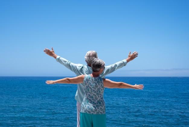 Vista traseira de dois idosos em pé no mar com os braços estendidos, olhando para o horizonte, aproveitando o verão e a liberdade