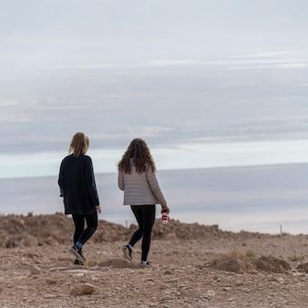 Vista traseira, de, dois, meninas adolescentes, andar, em, deserto, masada, judean, deserto, região mar morto, israel