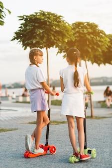 Vista traseira, de, duas meninas, ficar, ligado, empurre scooter, parque