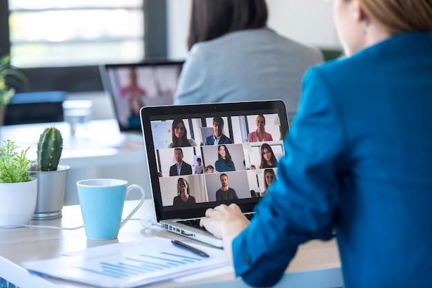 Vista traseira de duas mulheres de negócios falando em videochamada com diversos colegas em briefing online com laptop no escritório.