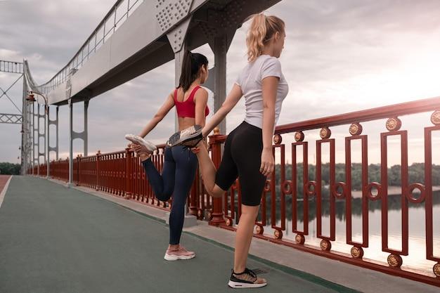 Vista traseira de duas mulheres esticando as pernas durante o treino na ponte enquanto observam a paisagem da cidade