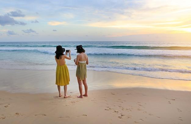 Vista traseira, de, duas mulheres, fotografado, a, bonito, paisagem, de, pôr do sol mar, com, telefone móvel