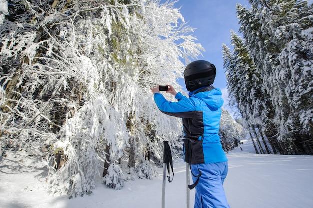 Vista traseira, de, esquiador, fazendo exame retrato, com, dela, telefone pilha