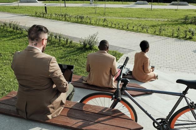 Vista traseira de executivos sentados em bancos e trabalhando ao ar livre no parque