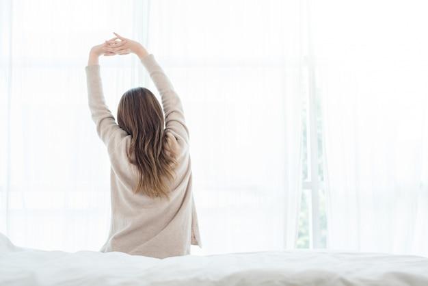 Vista traseira, de, feliz, bonito, jovem, mulher asian, acordar, em, manhã, sentar-se cama
