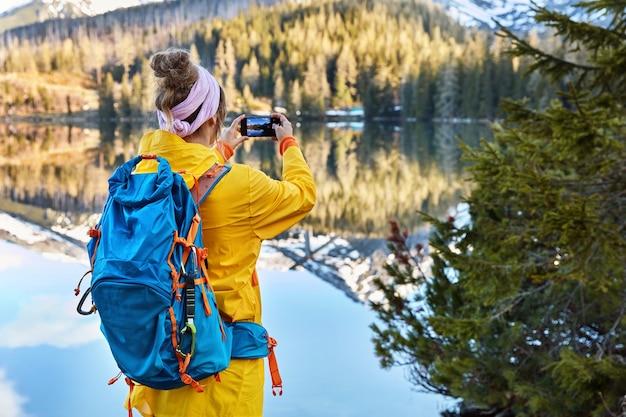 Vista traseira de fotos de turistas femininas ativas em um lago com montanhas em seu telefone inteligente