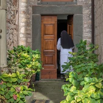 Vista traseira, de, freira, entrar, em, capela, radda, em, chianti, tuscany, itália