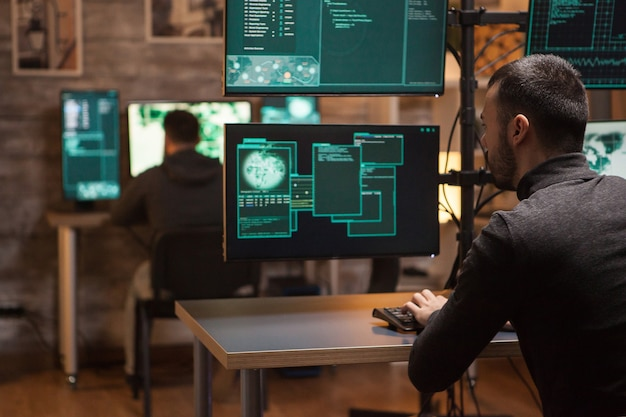 Vista traseira de hackers trabalhando na criação de um malware perigoso em computadores com várias telas.