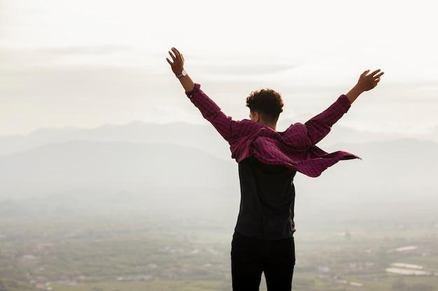 Vista traseira, de, homem jovem, com, levantado, mão