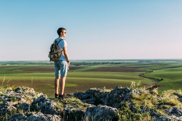 Vista traseira, de, homem jovem, ficar, cima, rocha, olhar, paisagem verde