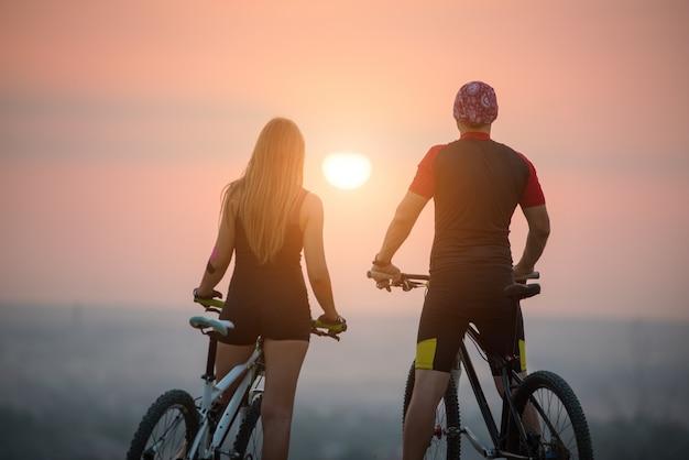 Vista traseira, de, homem mulher, ligado, montanha anda bicicleta, desfrutando, a, pôr do sol