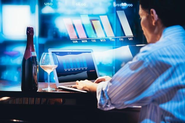Vista traseira, de, homem negócios, trabalhando, com, laptop, e, garrafa vinho