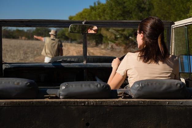 Vista traseira, de, homem, visto, através, pára-brisa, com, mulher, dirigindo veículo