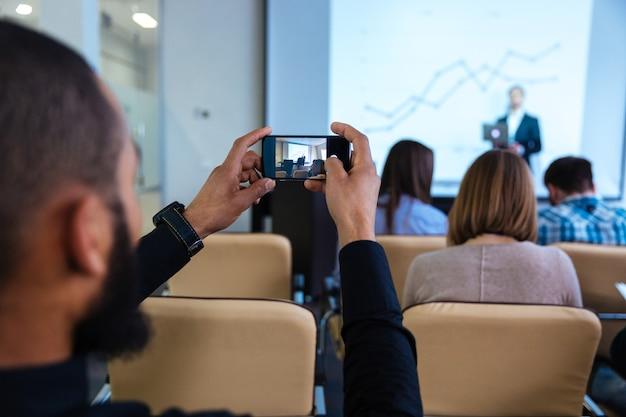 Vista traseira de jovem africano fazendo vídeo com smartphone em conferência de negócios na sala de reuniões