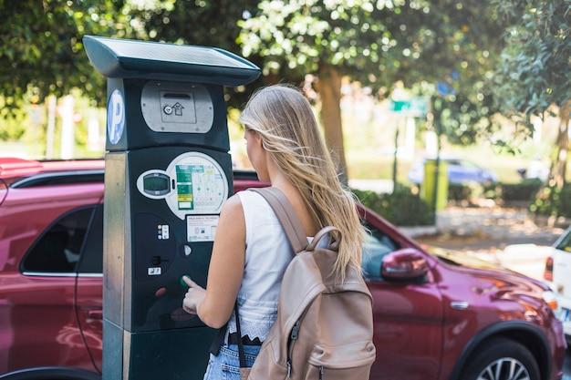 Vista traseira, de, jovem, femininas, pagando, para, estacionamento, rua
