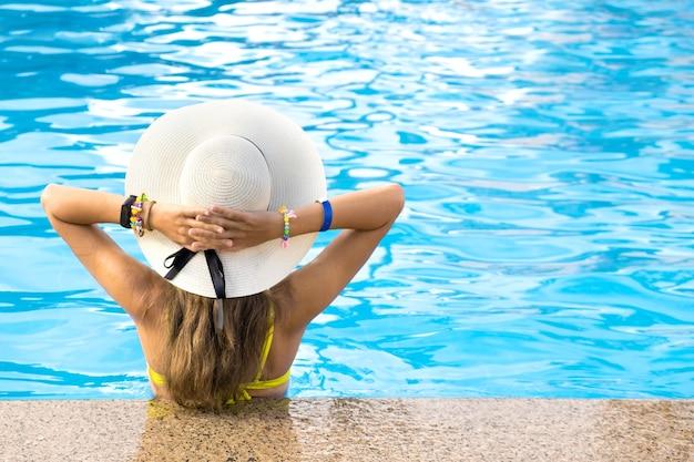 Vista traseira de jovem mulher com cabelo comprido, usando chapéu de palha amarelo relaxante na piscina quente de verão com água azul em um dia ensolarado.