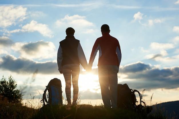 Vista traseira de jovens admirando o pôr do sol nas montanhas de mãos dadas. perto deles, há mochilas. o sol é visível entre suas silhuetas