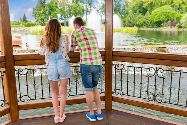 Vista traseira de jovens homens e mulheres apoiados na grade do gazebo de madeira em frente a uma cachoeira artificial em um parque com lago, fonte e árvores diferentes