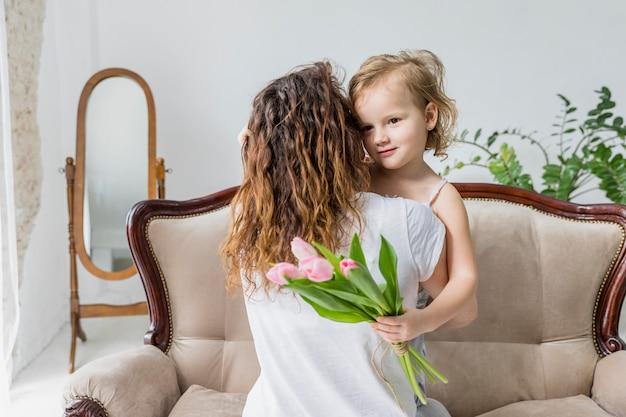 Vista traseira, de, mãe, carregar, para, dela, filha, segurando, tulipa cor-de-rosa, flores, ligado, sofá, casa