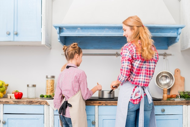 Vista traseira, de, mãe, e, dela, filha, cozinhar, alimento, cozinha