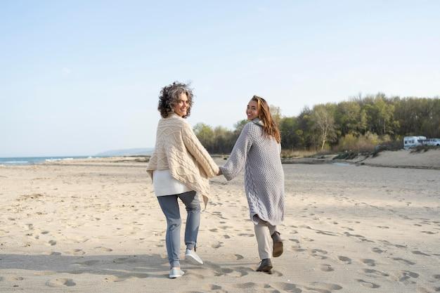 Vista traseira de mãe e filha na praia