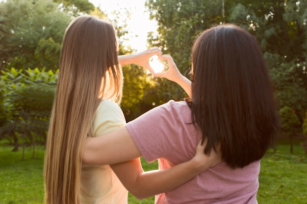 Vista traseira de melhores amigos fazendo um coração na luz do sol