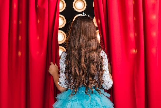Vista traseira, de, menina, estar, cortina, olhar fase