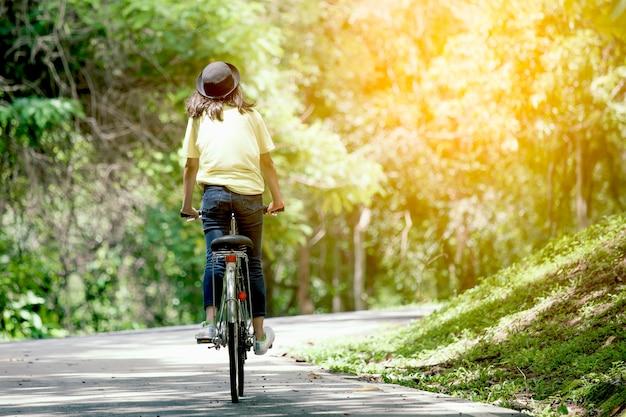 Vista traseira, de, menina jovem, bicicleta equitação, jardim, em, cor vintage, tom