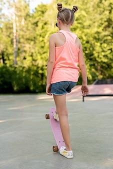 Vista traseira, de, menina, ligado, skateboard
