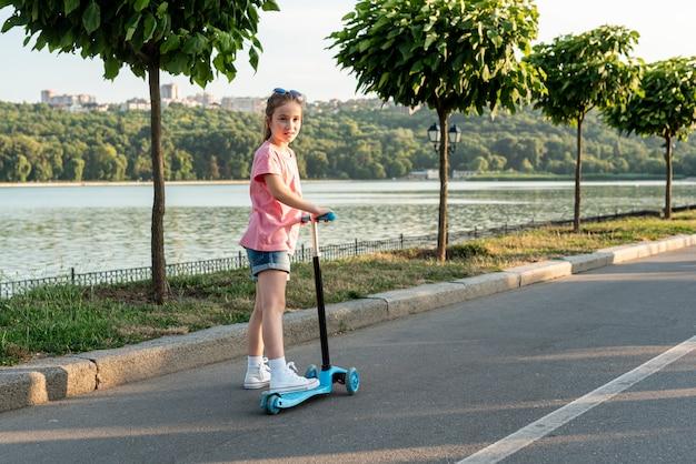 Vista traseira, de, menina, montando, azul, scooter