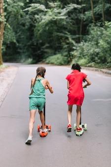 Vista traseira, de, menina, montando, empurre scooters, ligado, estrada