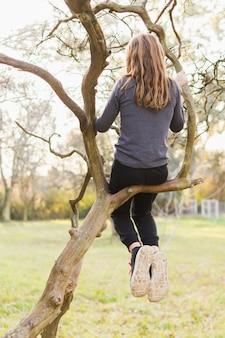 Vista traseira, de, menina, sentando, ligado, filial árvore, parque