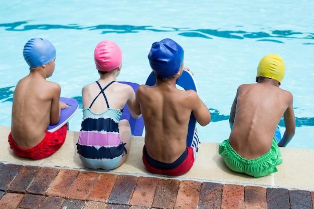 Vista traseira de meninas e meninos sentados à beira da piscina