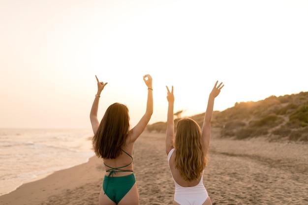 Vista traseira, de, meninas, em, biquíni, fazer, palavra, amor, com, sinal mão, ligado, praia