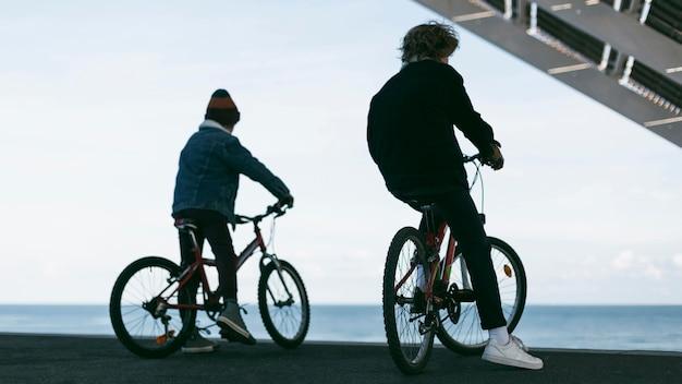 Vista traseira de meninos ao ar livre na cidade com suas bicicletas