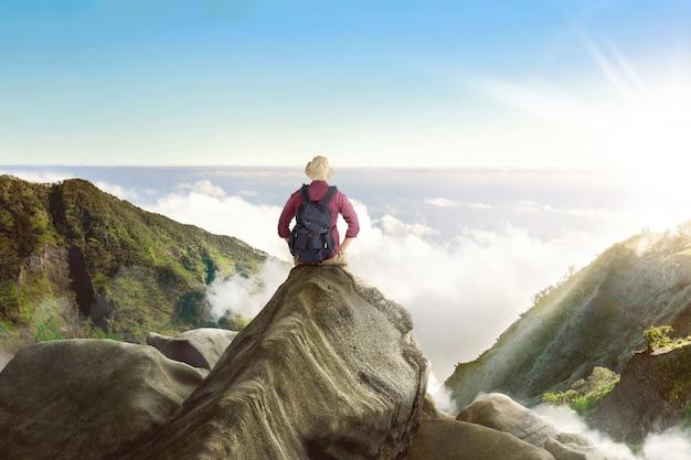 Vista traseira, de, mochileiro asiático, sentando, e, desfrutando, panorama