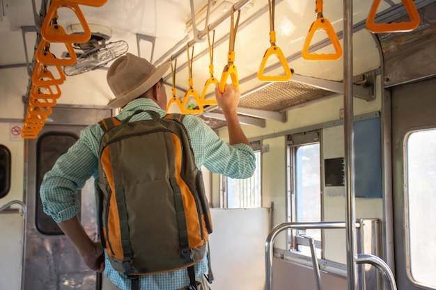 Vista traseira, de, mochileiros asiáticos, segurando, corrimão, dentro, a, trem público, ligado, férias