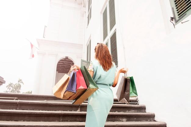Vista traseira, de, mulher asian, com, bolsas para compras, andar