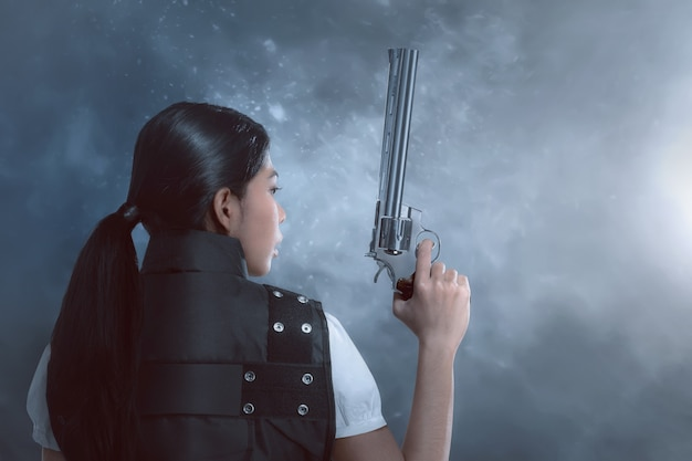 Vista traseira, de, mulher asian, com, uniforme polícia, segurando, armas