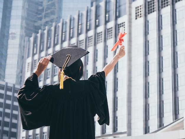 Vista traseira, de, mulher asiática, com, boné graduação, e, vestido, segurando, diploma