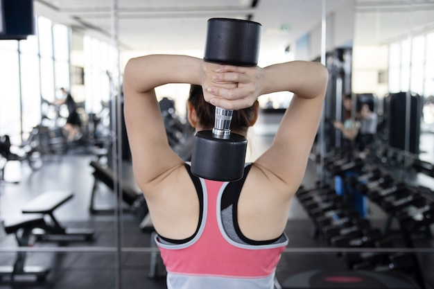 Vista traseira de mulher asiática exercitando seu tríceps com dumbell