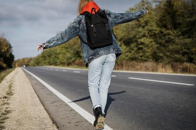 Vista traseira de mulher caminhando na estrada