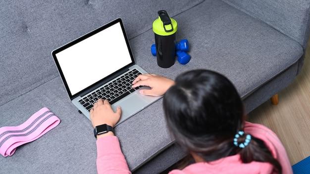 Vista traseira de mulher com excesso de peso, assistindo a um vídeo de treinamento de fitness no laptop no sofá em casa.