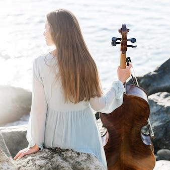 Vista traseira de mulher com violoncelo à beira-mar