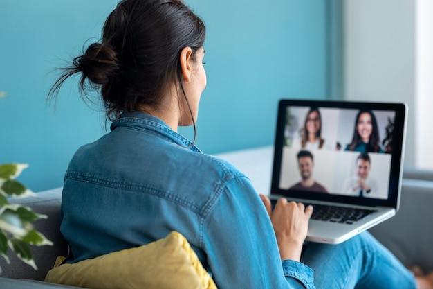Vista traseira de mulher de negócios, falando em videochamada com diversos colegas em briefing online com laptop no sofá em casa.