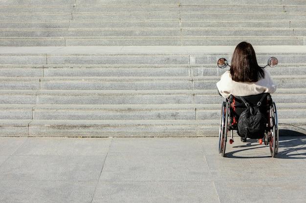 Vista traseira de mulher em cadeira de rodas se aproximando de escadas