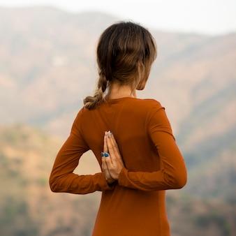 Vista traseira de mulher em pose de ioga ao ar livre na natureza