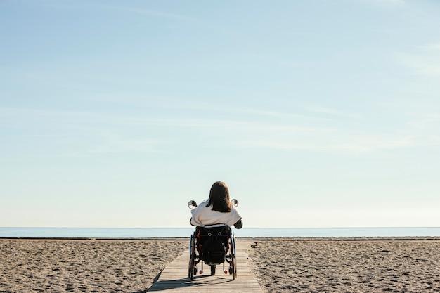 Vista traseira de mulher em uma cadeira de rodas na praia
